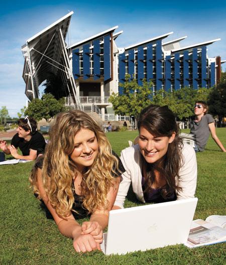 Zwei Studentinnen lernen auf dem Rasen des Campus