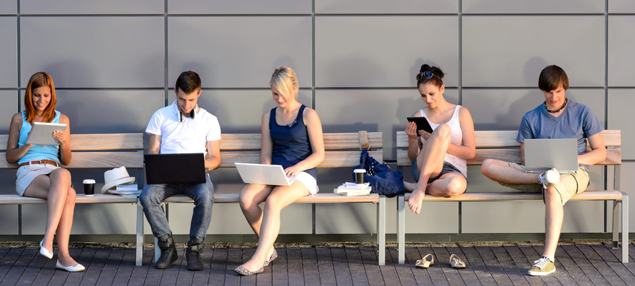 Studenten arbeiten auf einer Bank im Freien